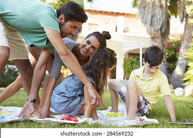 Family Playing Balancing Game In Garden