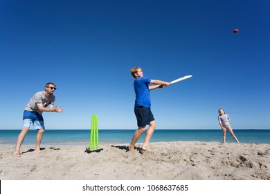 A family playing Beach Cricket