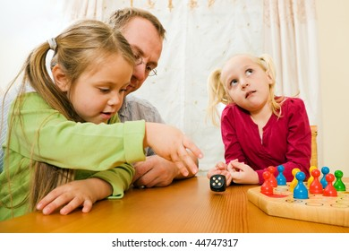 Family playing a board game at home in their leisure time, the setting is their living room