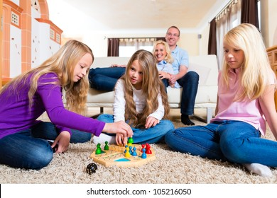 Family playing board game ludo at home on the floor