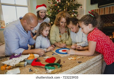 Family are playing board games together in the living room of their home at christmas time.