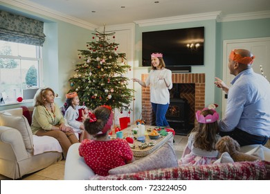 Family are playing charades at christmas time in the living room of their home. It's the mother's turn and everyone is trying to guess.