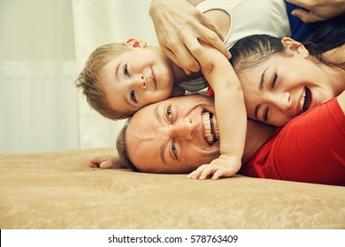 Family playing with child at home. Dad, mom and son having fun