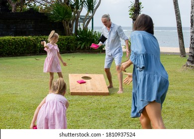 Family playing cornhole game by the sea on sunny summer day. Parents and children playing bean bag toss