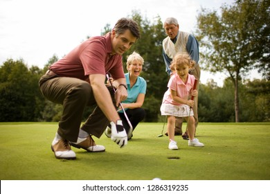 Family playing golf together on a golfing green.