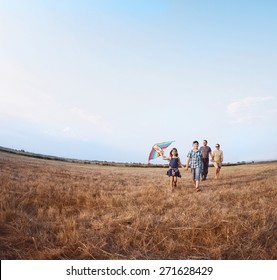 Family playing with kite on the summer field