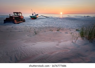 Family playing on beach at abandoned boat and vessel at sunset
