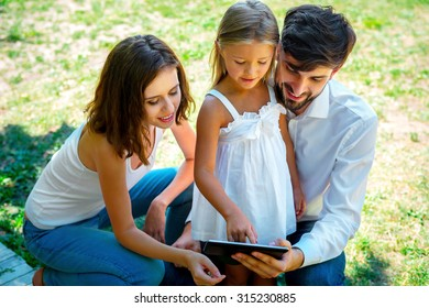 Family playing on the tablet in the park. Smiling father holding the tablet and daughter is playing on it. Sunny day