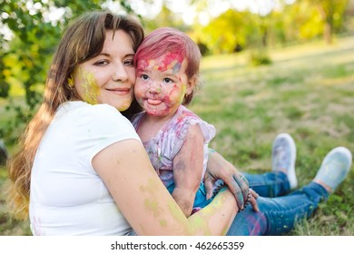 Family playing in the park. Family painted in the colors of Holi Festival