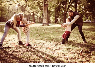 Family playing with rope in park.