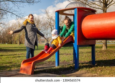 Family playing at slide in public playground, Zagreb, Croatia.