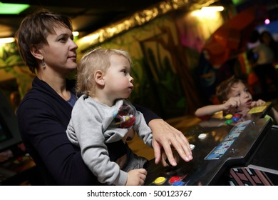 Family playing in the slot machines at an amusement park