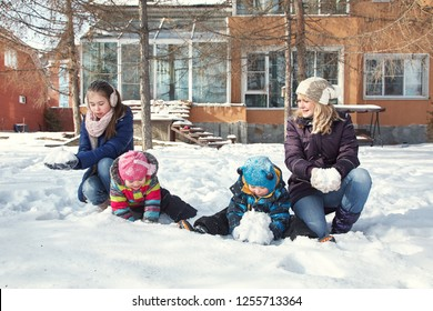 family playing with snow in the yard of his house in the winter outdoors