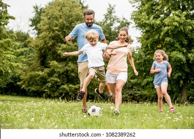 Family playing soccer in the park and having fun