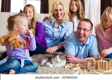 Family playing with toy blocks and a cat at home on the floor