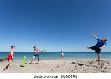 A family playing the traditional Aussie game of Beach Cricket