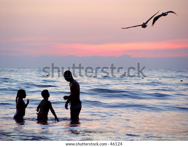 Family playing in the water at sunset