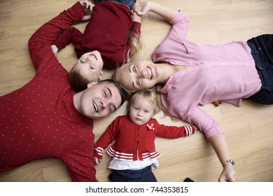 family in the playroom lies on the floor. are playing