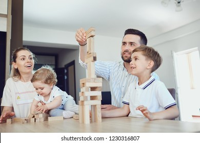 A family plays board games sitting at a table indoors.