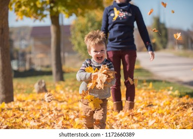The family plays with fallen yellow leaves for a walk in the village. Family holidays