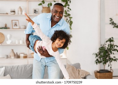 Family playtime. Happy African American grandfather playing silly game with his granddaughter at home, copy space