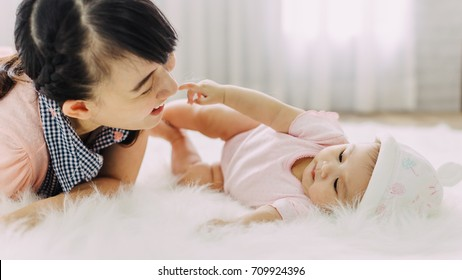 Family portrait of Asian people : 4 months baby feeling happy loving and smiles while playing with her mother.