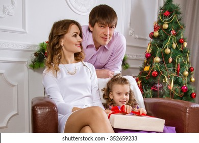 Family portrait with the child looking at the camera near a Christmas fir-tree.