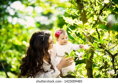 family portrait closeup spring summer  outdoors with grass and flowers  park beautiful happy  woman  mom and her  daughter in a white dress lifestyle