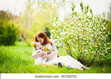 family portrait closeup spring summer cooking outdoors with grass and flowers beautiful happy pregnant woman with red hair and her eldest daughter in a white dress lifestyle