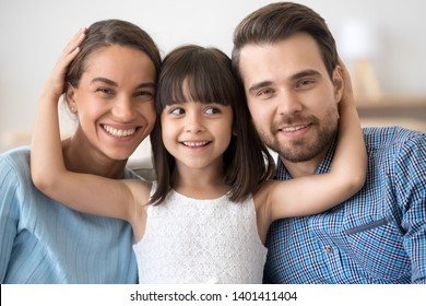 Family portrait of cute little daughter stand in between smiling young parents hugging them, happy mom and dad posing together with small girl child looking at camera laughing and cuddling