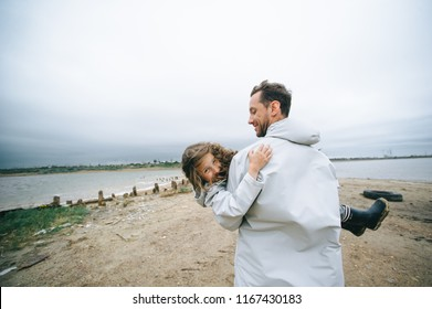 family portrait of dad and dauther in raincoat near the sea