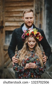 Family portrait, expacting couple. Man hugs tender pregnant woman in flower wreath from behind standing outside. Autumn style