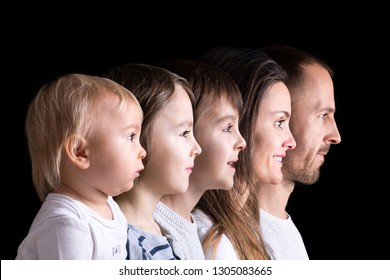 Family portrait of father, mother and three boys, profile picture of them all in a row, isolated on black background, color version