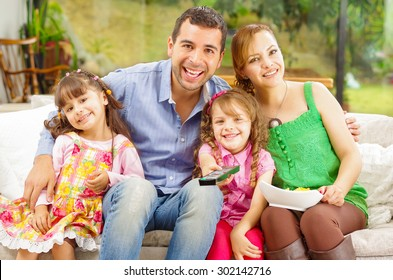 Family portrait of father, mother and two daughters sitting together in sofa smiling towards camera embracing each other.