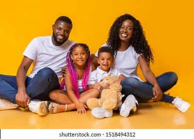 Family portrait. Happy mother and father with their children sitting on floor and posing to camera over yellow studio background