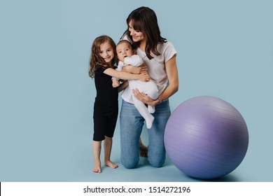 Family portrait of a happy mother with two daughters, one little, one infant, next to a yoga ball over blue background.