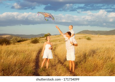 Family portrait. Happy parents with baby smiling on a wheat field in sunlight. Outdoors.