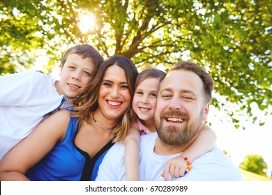 Family portrait of happy parents sitting together with their children, looking at camera and smiling in summer