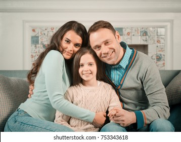 Family portrait of happy parents and their daughter at home
