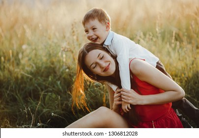 Family portrait, nature. Charming mom and son play on the lawn before the sunset
