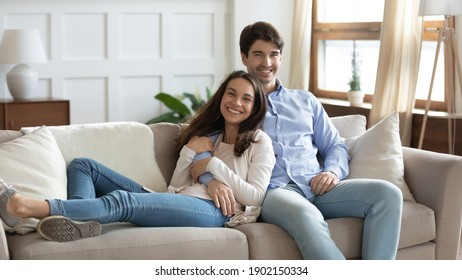 Family portrait smiling woman and man hugging, sitting on cozy couch in living room at home, happy young couple posing for photo, loving wife and husband cuddling, looking at camera together