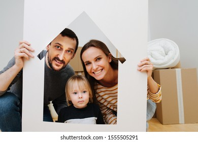 Family portrait, taken through house resembling frame. Mother, father and their little son together in a new apartment filled with stacks of unpacked boxes. Moving to a new home concept.