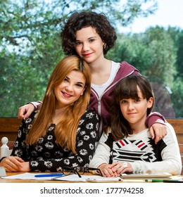 Family portrait of three adolescent sisters together at desk.