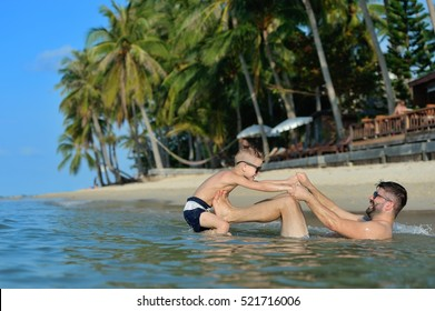 Family portrait in water: father and son are fighting in water, they are having fun. Little cute blond boy wins - beautiful empty tropical beach on the background