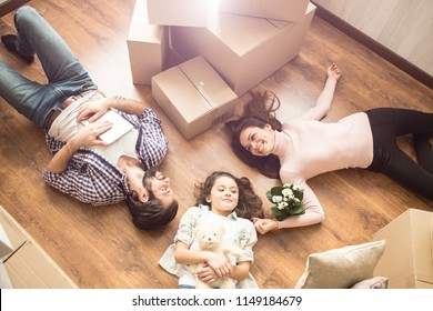 Family portrait where everybody is lying on the floor. Small girl has her teddy bear in the hnds. There is a plant near young woman's hand. Young man is holding a tablet or notebook.