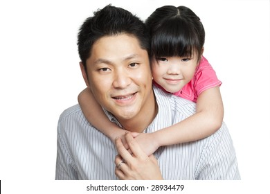 Family portrait of young Chinese father piggybacking little daughter dressed in pink. Shot in studio, isolated in white