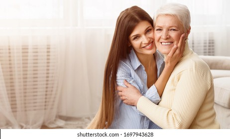 Family portrait. Young woman hugging and looking at camera at home, copy space