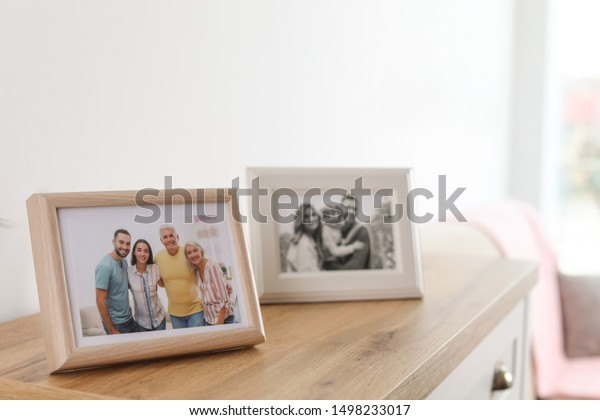 Family portraits in frames on cabinet indoors