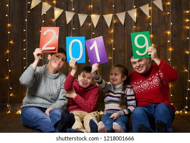 family posing with 2019 new year text, sitting on dark wooden background with christmas lights and flags, and having fun. Winter holiday concept.