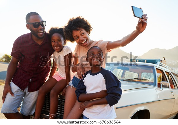 Family Posing For Selfie Next To Car Packed For Road Trip